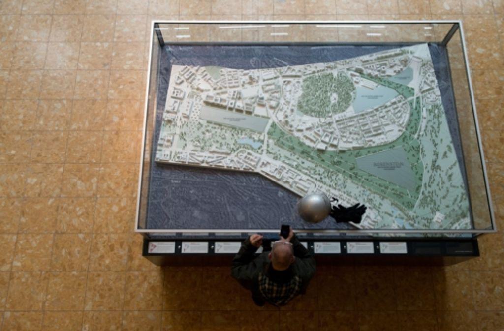 Ein Mann steht am 19.02.2013 in Stuttgart  an einem Modell, das zeigt, wie ein Teil der Innenstadt nach der Vollendung des Bahnprojekts Stuttgart 21 aussehen soll. Foto: dpa