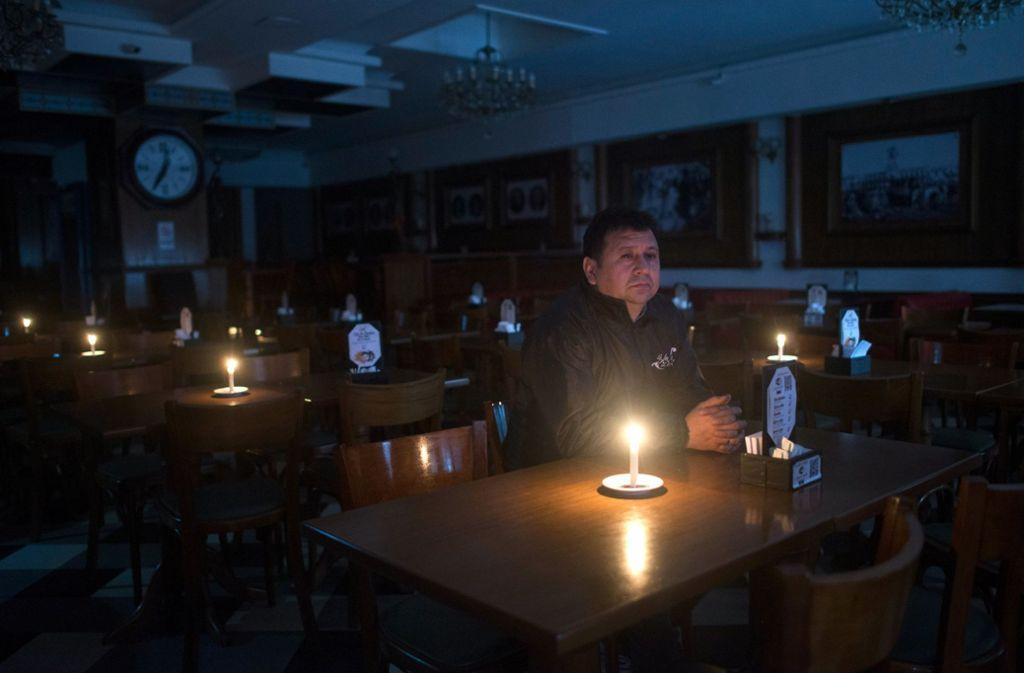 Ein Kunde sitzt während eines Stromausfalls in einer Bar an der Avenida de Mayo in Buenos Aires. Foto: dpa