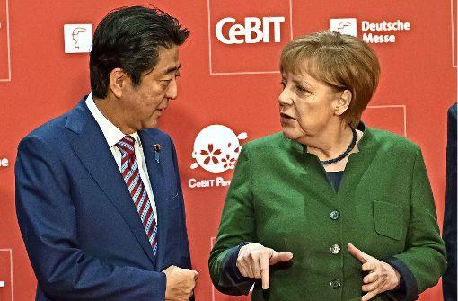 Bundeskanzlerin Angela Merkel und  der japanische  Ministerpräsident Shinzo Abe sprechen  vor der Eröffnung der  Cebit – Japan ist diesmal Partnerland. Foto: dpa