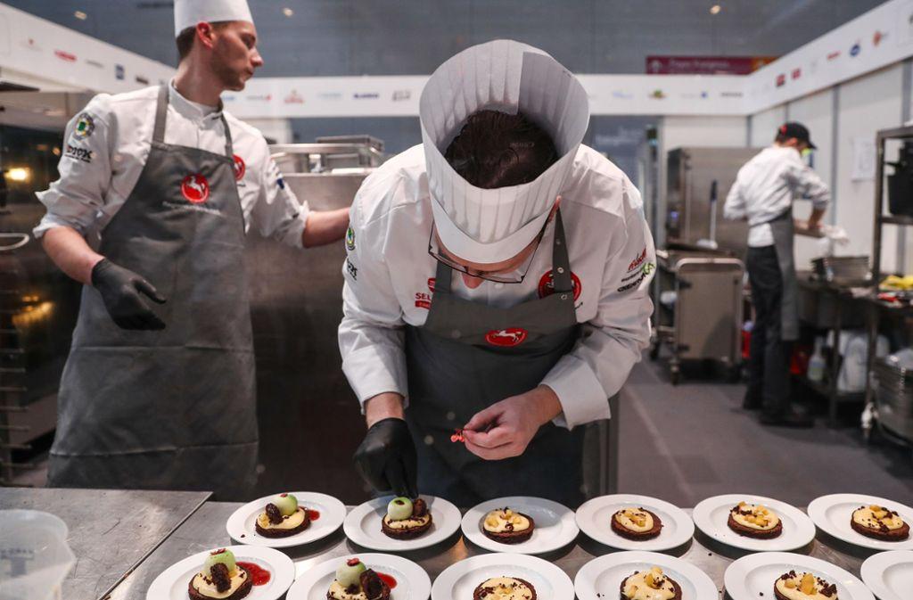 """Die Köche vom Team ·Deutschland· arbeiten bei der ·Olympiade der Köche"""" in einer Halle der Messe in ihrer kleinen Küche. Unter dem Motto «grenzenlos kochen» messen sich etwa 2000 Köche in Teams aus mehr als 50 Nationen im weltgrößten Berufswettbewerb. Foto: dpa/Christoph Schmidt"""