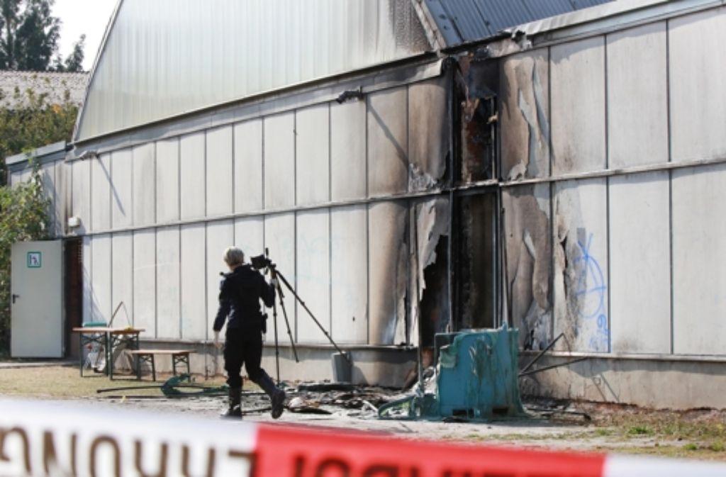 Eine Kriminalpolizistin nimmt nach einem Feuer in einer Notunterkunft für Flüchtlinge in Friemar  Spuren auf. Foto: dpa