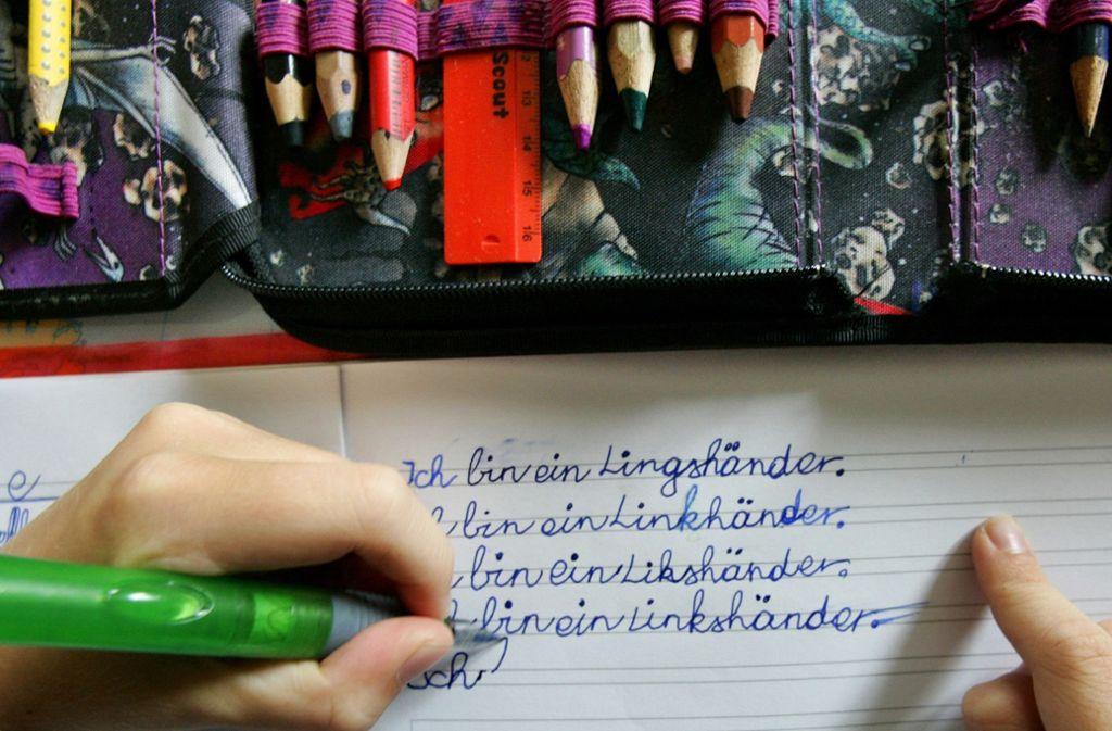 Mit seiner linken Hand schreibt ein Grundschüler in sein Rechtschreibübungsheft. Linkshänder lassen sich laut einer neuen Studie niemals vollständig zu Rechtshändern umpolen. Foto: dpa