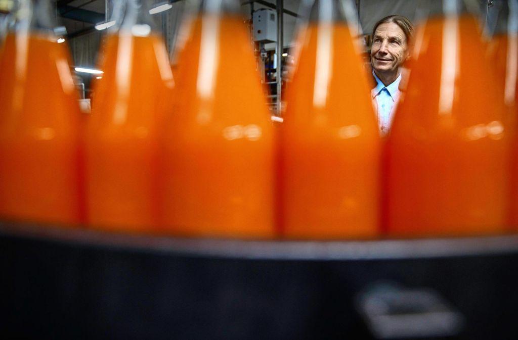 Matthias Maier verschwindet schier hinter den Flaschen, die bei Beutelsbacher Fruchtsäfte mit hochwertigem Inhalt gefüllt werden. Foto: Gottfried Stoppel