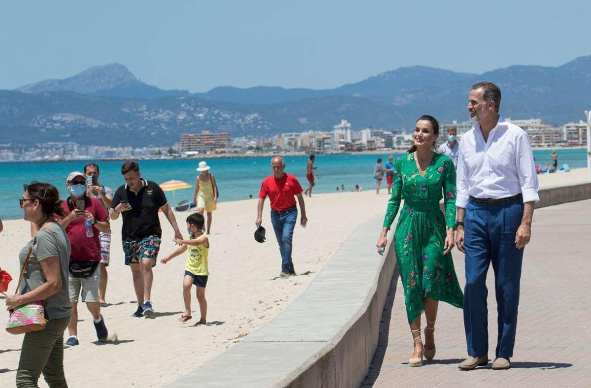 Spaniens König Felipe und Frau Letizia schlendern an der Promenade der Playa de Palma entlang. Sie machen traditionell im August Urlaub auf der Baleareninsel. Foto: AFP/JAIME REINA