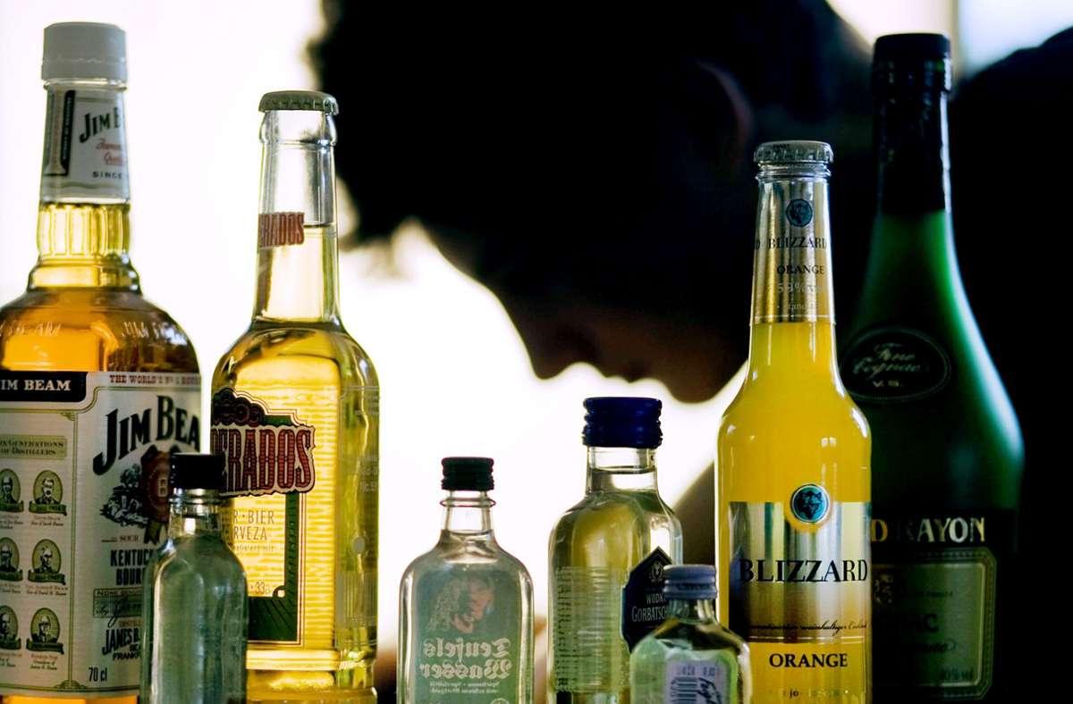 Ein Jugendlicher sitzt hinter Flaschen mit Alkohol. Die Zahl der Kinder und Jugendlichen, die mit Alkoholvergiftung im Krankenhaus landen, nimmt insgesamt weiter ab. Foto: Jens Büttner/dpa