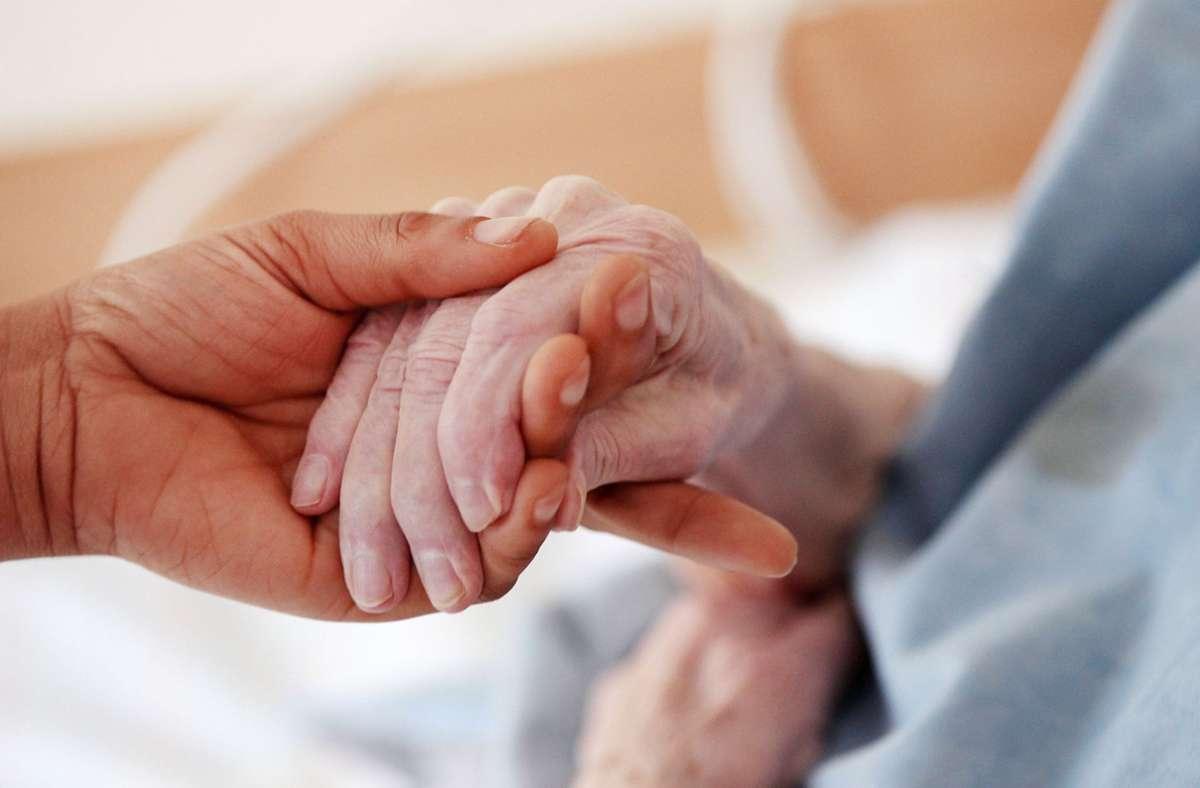Eine Pflegerin hält in einem Altenheim die Hand einer Bewohnerin (Symbolbild). Foto: Oliver Berg/dpa