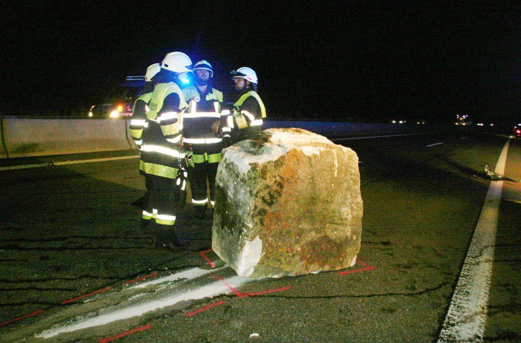 Feuerwehrleute neben dem drei Tonnen schweren Steinquader auf der  A81 Foto: kamera24