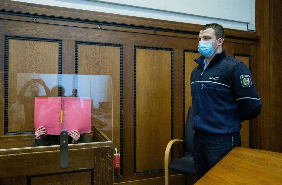 Die Verurteilte verbirgt ihr Gesicht beim Foto im Gerichtssaal. Foto: dpa/Rolf Vennenbernd