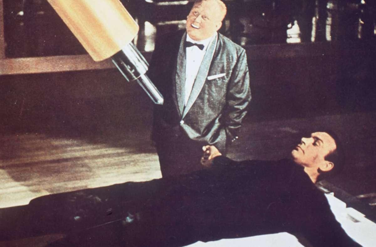 Symbolträchtige Szene: Der Schurke Goldfinger (Gert Fröbe) will den auf einen Tisch geschnallten  James Bond (Sean Connery) mit einem Laser erledigen, der ihn zuerst im  Schritt trifft. Foto: imago images / United Archives