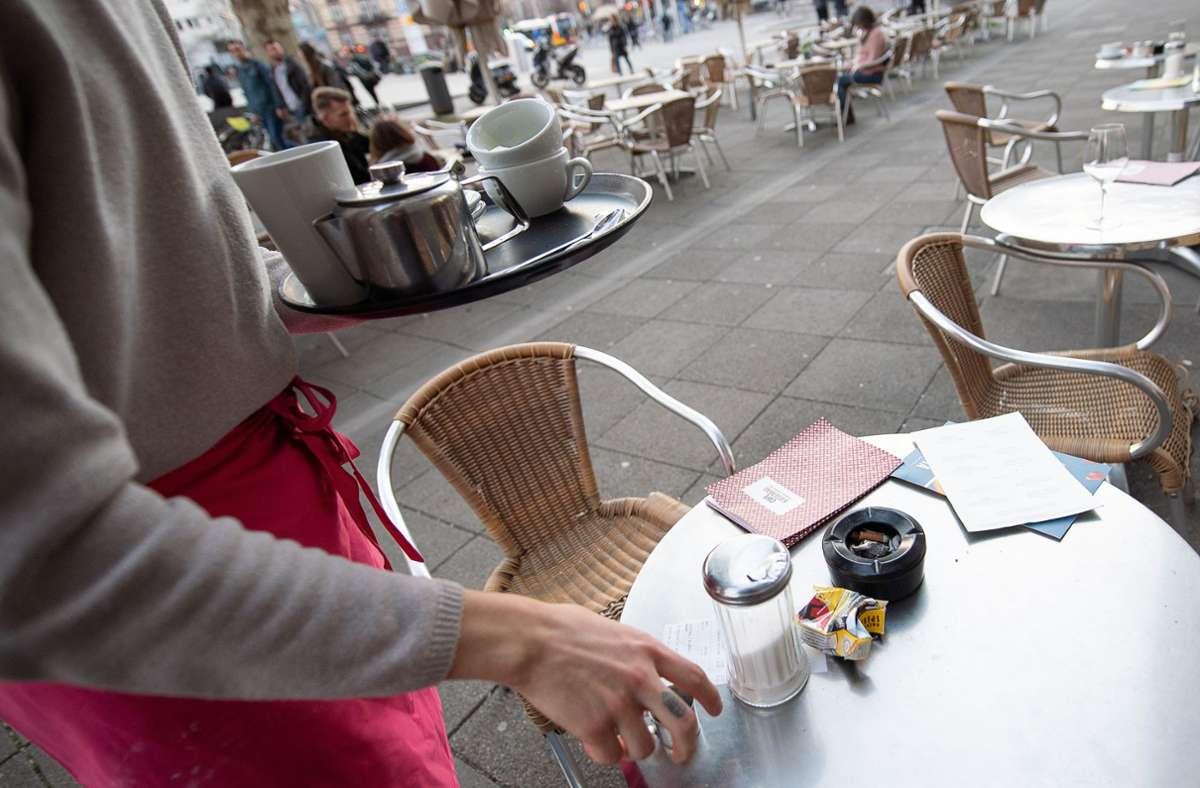 Ein Kellner räumt den Tisch eines Stuttgarter Restaurants ab. In Restaurants finden viele Studenten Nebenjobs. (Archivbild) Foto: dpa/Sebastian Gollnow