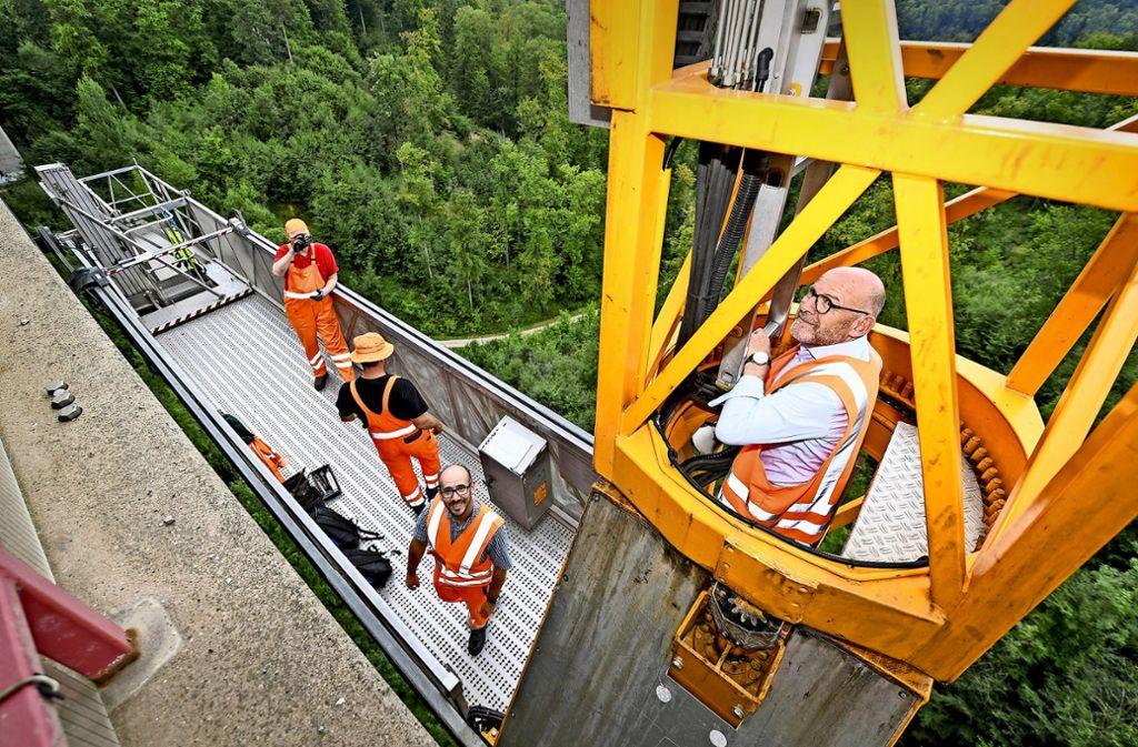 Luftiger Ausflug für den Verkehrsminister: Winfried Hermann (rechts) klettert in 50 Metern  Höhe über eine Leiter. Foto: dpa