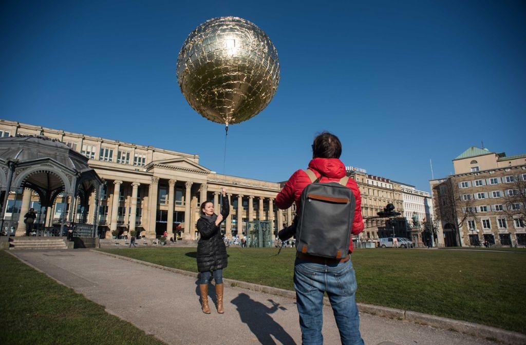 Die Künstlerin Marie Lienhard lässt ihren goldenen Ballon auf dem Schlossplatz steigen. Foto: Lichtgut/Max Kovalenko
