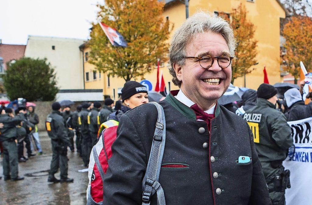 Heinrich Fiechtner strahlt trotz  Gegendemonstranten vor der Landesversammlung seiner Partei in Kehl. Foto: dpa