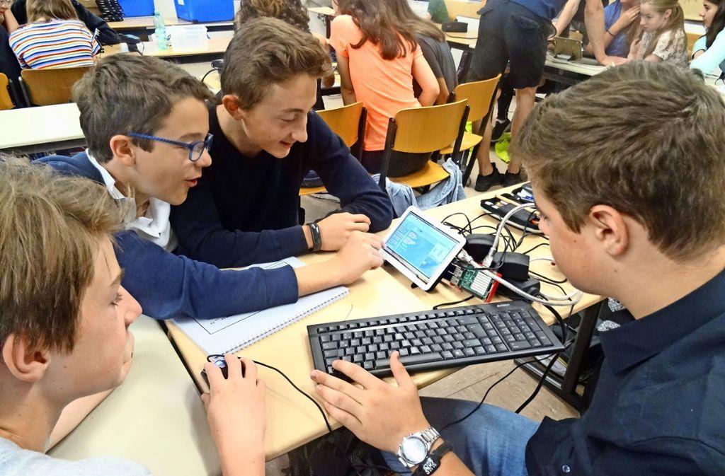 Paul, Jonas, Julius und Matteo (v.l.) programmieren ein intelligentes Schließfach. Foto: Theresa Ritzer