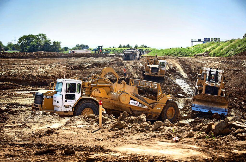Ein Scraper (links) im Einsatz. Zur Not schiebt ihn der Bulldozer an. Foto: Michael Steinert