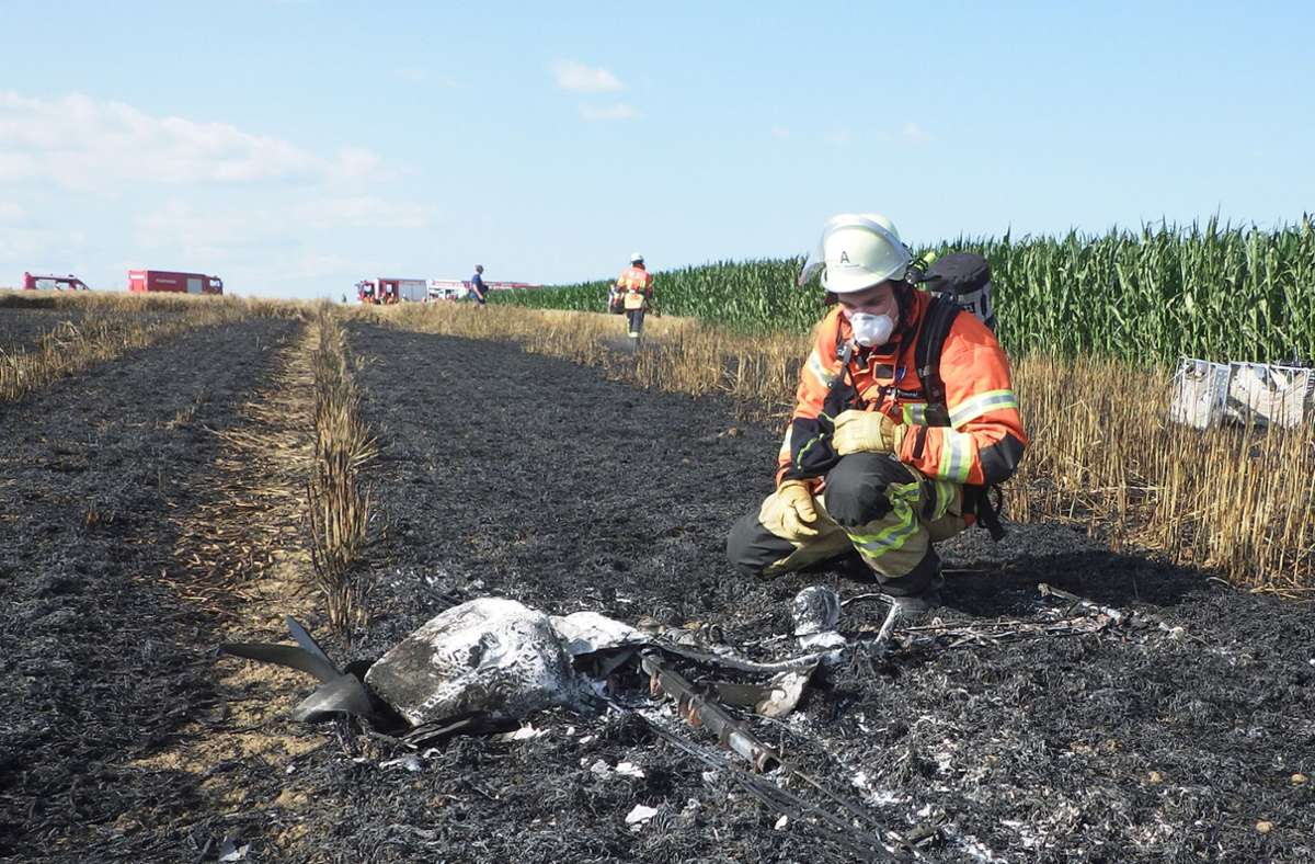 Ein Feuerwehrmann betrachtet das komplett zerstörte Modellflugzeug. Foto: Feuerwehr Ditzingen/z