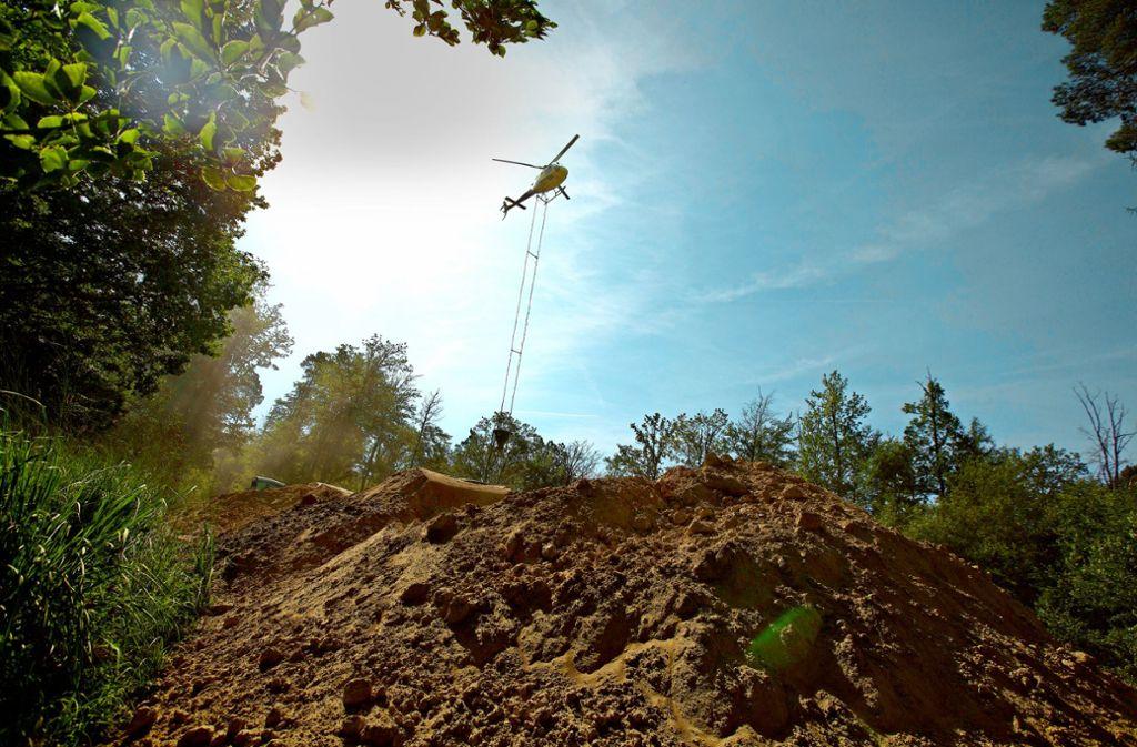Während der Hubschrauber über dem Startplatz steht,  kippt ein Radlader Kalk  in den Streubehälter. Foto: