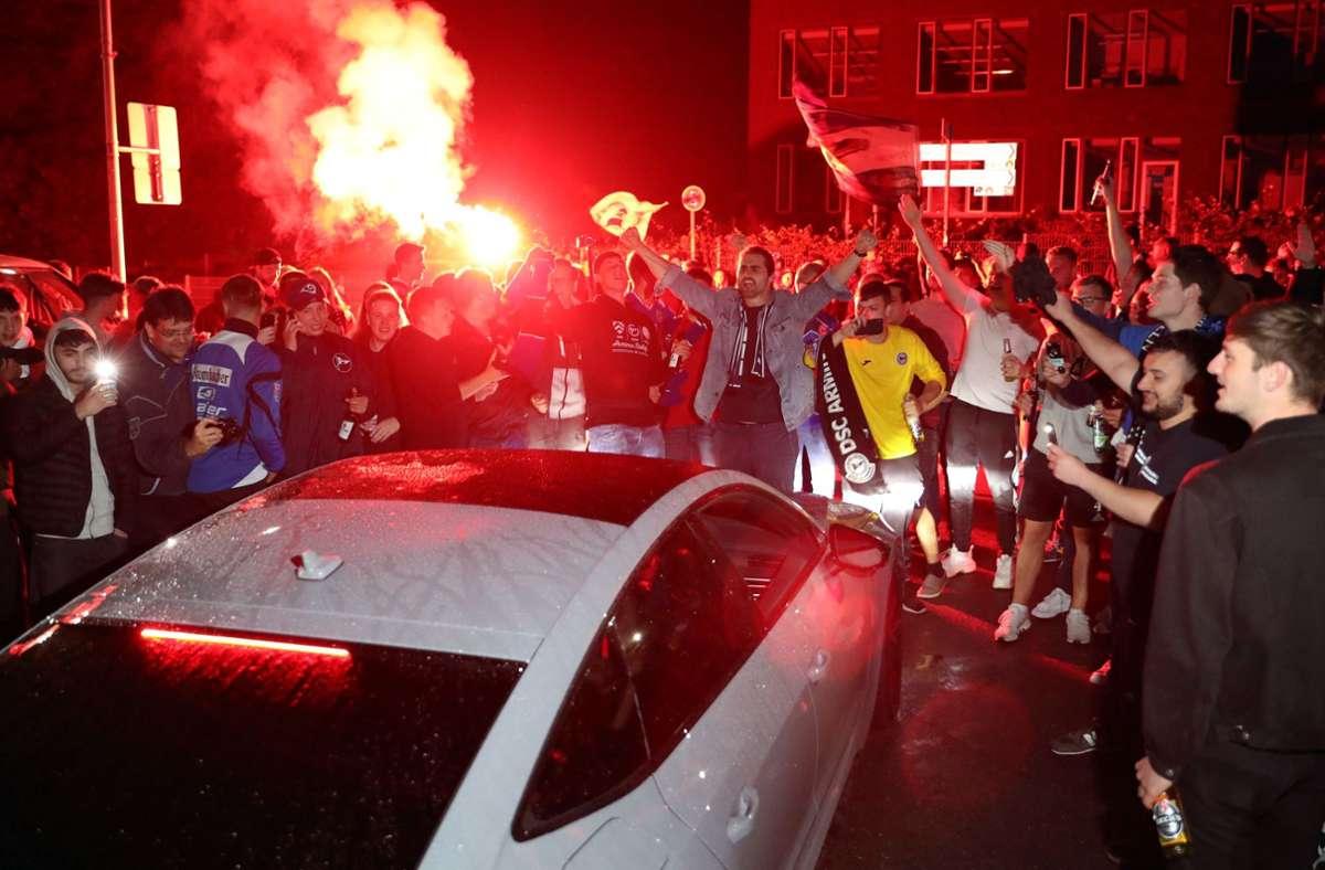Bielefeld Fans feiern vor dem Stadion den Sieg ihrer Mannschaft. Foto: dpa/Friso Gentsch