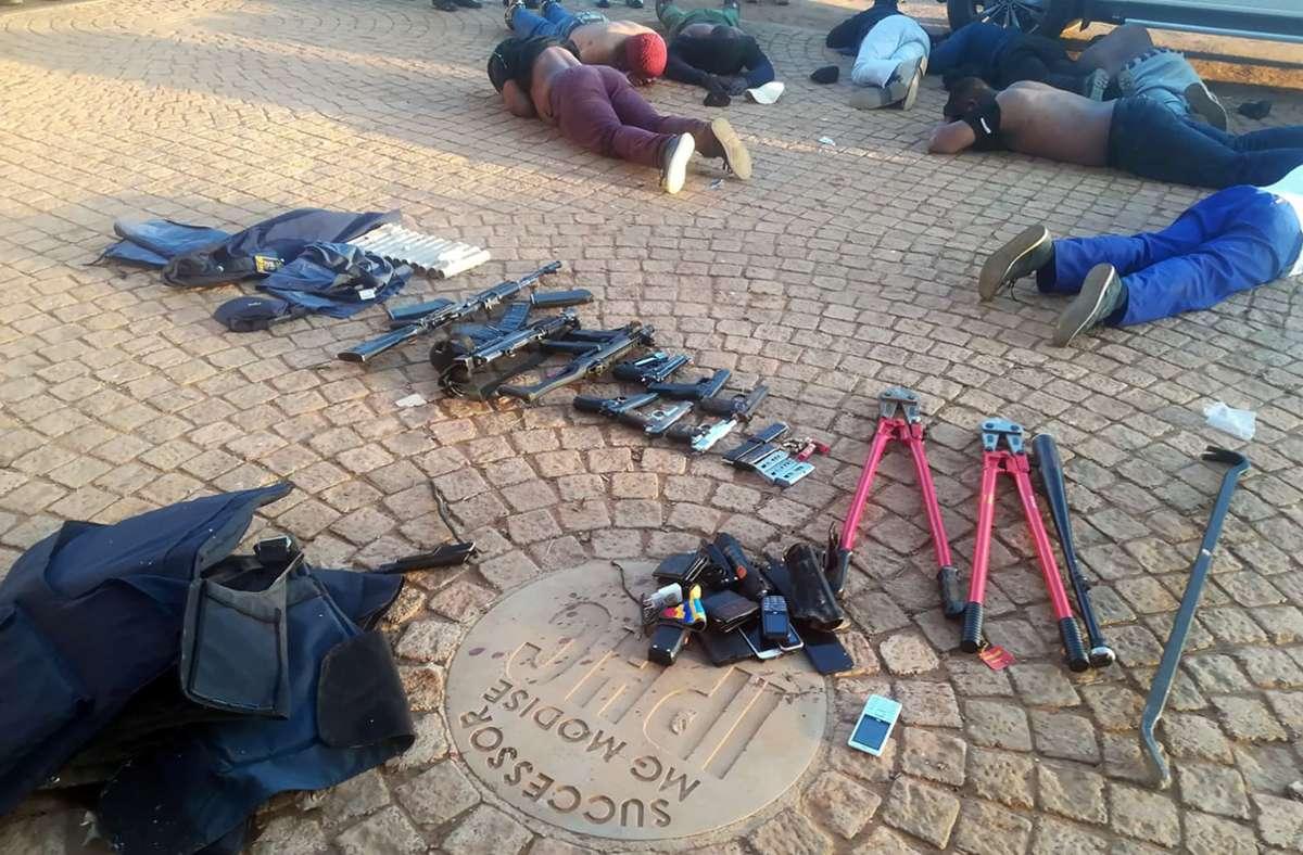 Einige Tatverdächtige liegen nach dem Polizeieinsatz auf dem Boden. Foto: dpa