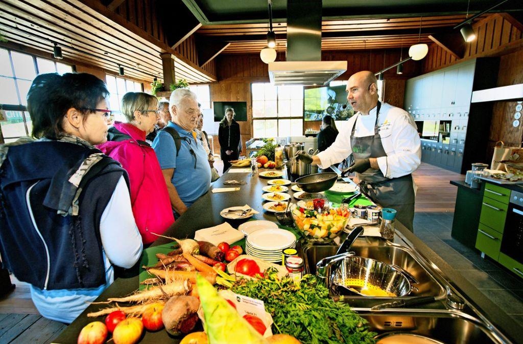 In der neuen Schauküche im Gartensaal des Freilichtmuseums Beuren  lässt sich   Eberhard Braun (rechts) von den Besuchern in Töpfe und Pfannen schauen. Foto: Horst Rudel