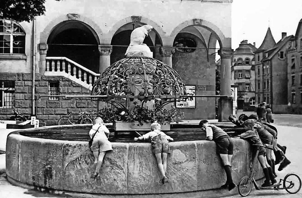 Kinder im Lederhosen-Look lehnen sich über den Biberbrunnen.  Lange haltbar sollte   das gute Stück damals sein. Deshalb wurde es auch regelmäßig mit Fett  eingerieben. Foto: privat