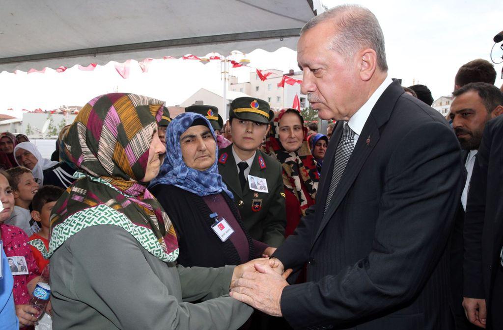 Erdogan spricht bei der Beisetzung einer Mutter und ihres Babys den Hinterbliebenen sein Beileid aus. Foto: AFP