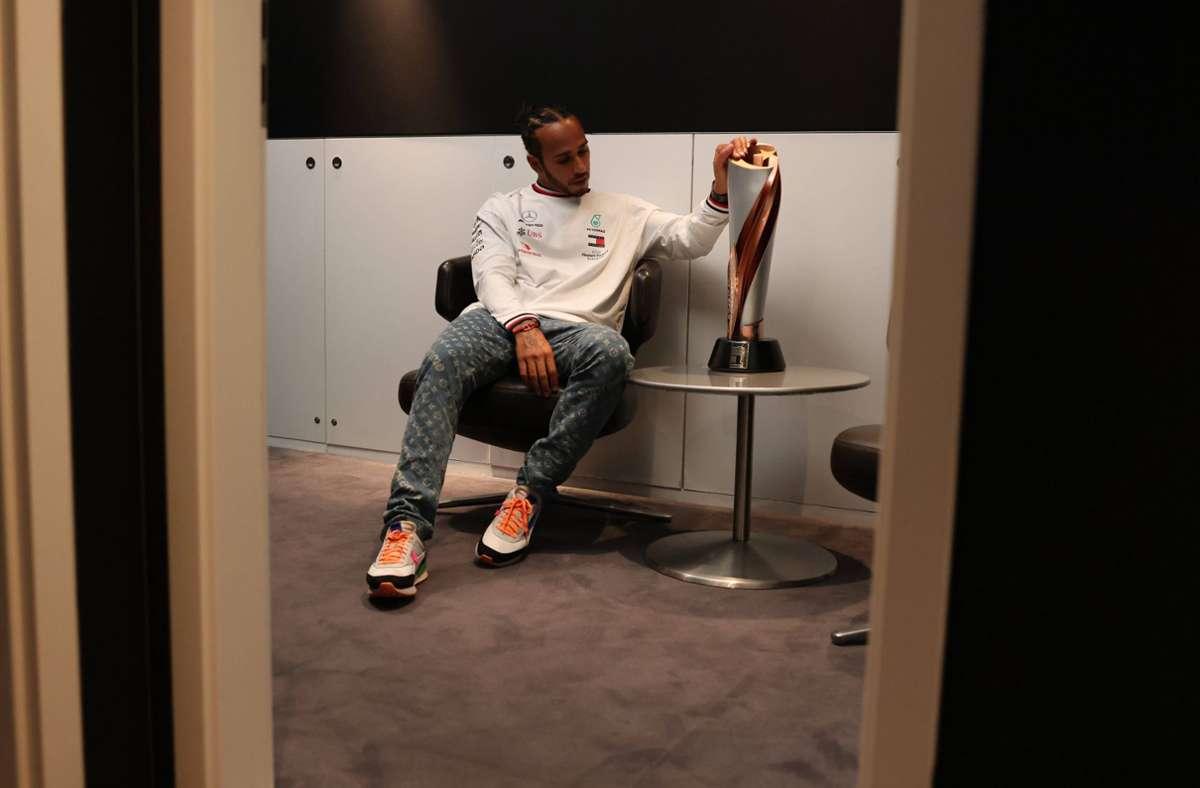 Rekordweltmeister Lewis Hamilton mustert in einer stillen Minute in einem Nebenzimmer den Pokal für den Sieger des Großen Preises der Türkei. Foto: imago/Motorsport Images