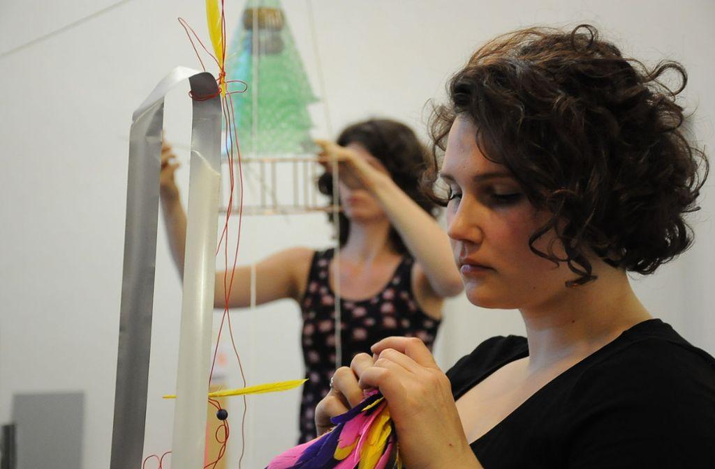 Mit einer Performance gibt Julia Römpp im Werkstatthaus die Initialzündung für das Entstehen einer Installation. Im Hintergrund eine Vernissagen-Teilnehmerin, die spielerisch mitwirkt Foto: Georg Linsenmann