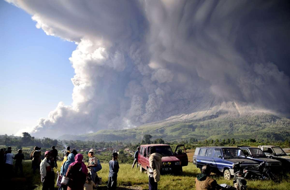 Orang-orang menyaksikan gunung berapi Sinabang meletus.  Gunung berapi setinggi 2.500 meter ini merupakan salah satu dari lebih dari 120 gunung berapi aktif di Indonesia.  Foto: Belum diverifikasi / AP / DP