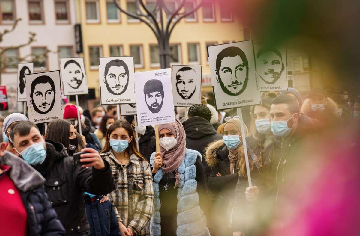 Bei der Gedenkfeier zeigen die Bürger Plakate mit Bildern der Opfer. Foto: dpa/Andreas Arnold