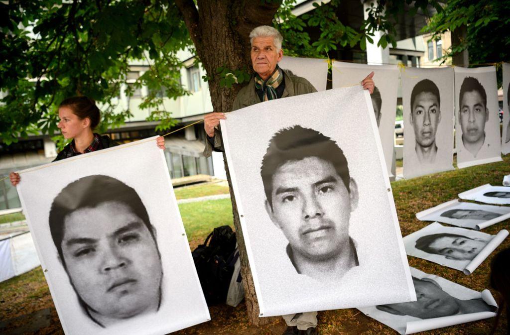 Rüstungsgegner zeigen vor dem Landgericht Stuttgart bei einer Mahnwache Bilder von mexikanischen Opfern. Foto: dpa