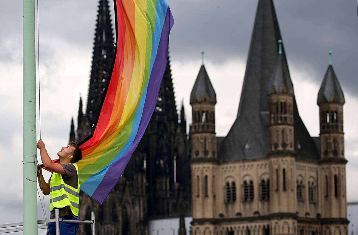 """Ein Arbeiter hängt nach der Entscheidung im Bundestag über die """"Ehe für alle"""" vor der Kulisse des Doms eine Regenbogenfahne auf. Nach den Äußerungen der vatikanischen Glaubenskongregation über die Segnung homosexueller Partnerschaften appellieren schwule und lesbische Katholiken an die deutschen Bischöfe Foto: dpa/Oliver Berg"""