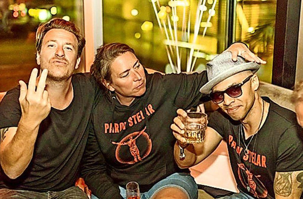Parov Stelar (llnks) mit seiner Tourmanagerin und seinem Sänger bei der After-Show-Party in der Bar Waranga. Foto: Andreas Engelhard