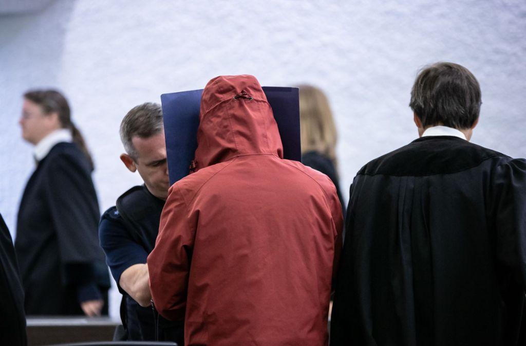 Der Angeklagte schützt sich beim Betreten des Saals vor den Blicken der Zuschauer. Foto: Lichtgut/Julian Rettig