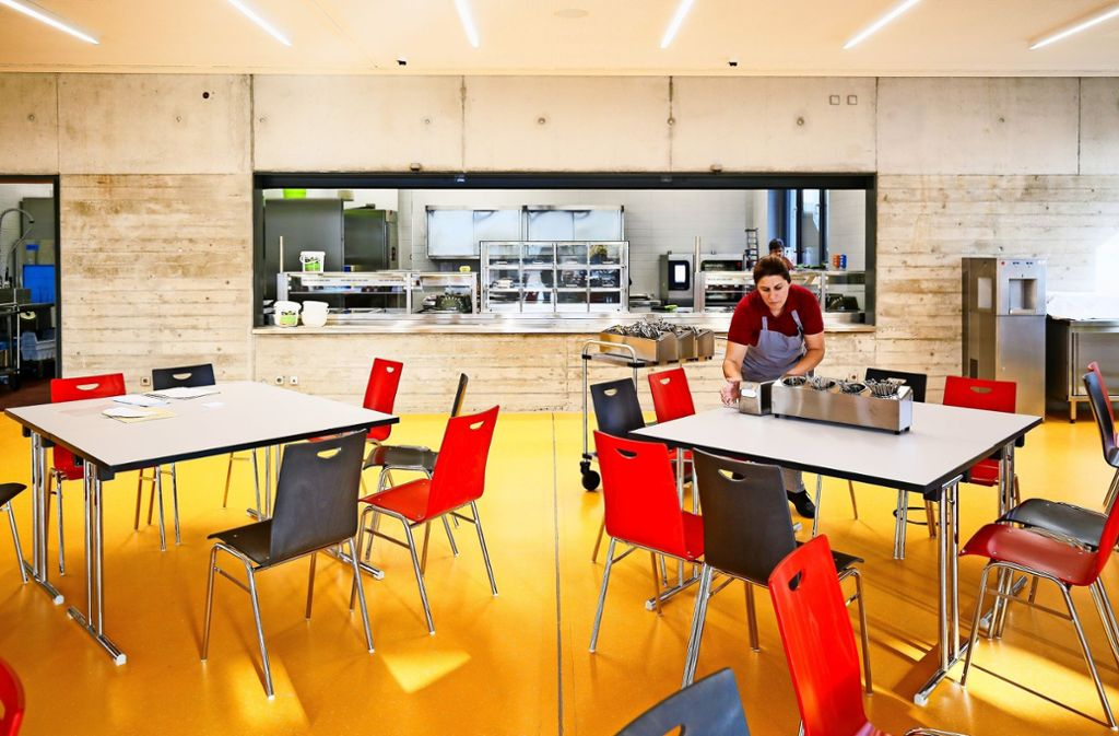 Ein freundlicher Raum und viele Tische für je acht Kinder: Das Besteck wird am Tisch hergerichtet.Die Küche ist in Funktionsbereiche aufgeteilt. Rechts ist  die letzte Station – die Ausgabe. Foto: factum/Granville