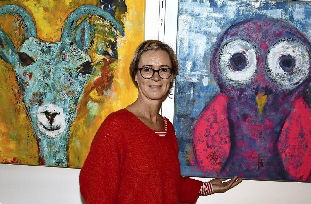 Farbenfroh und mehrschichtig – Biggi Besemer mit zwei ihrer Gemälde. Foto: Mathias Kuhn