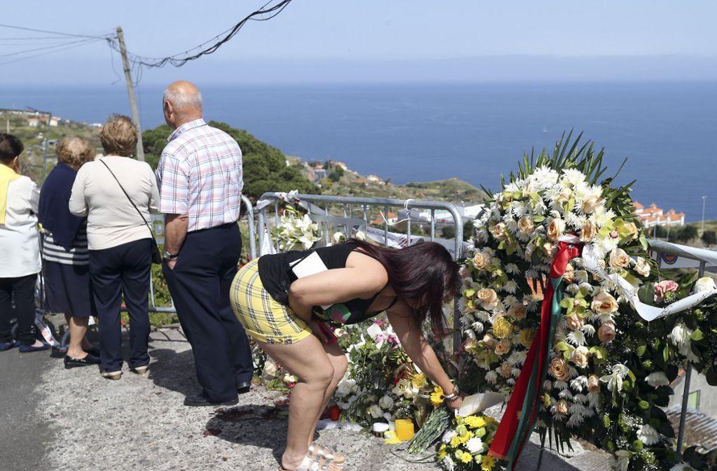 Menschen gedenken am Umglücksort auf Madeira den Toten. Foto: AP