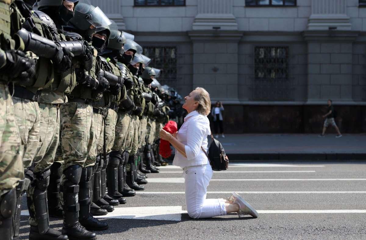 Minsk: Eine Demonstrantin kniet vor Bereitschaftspolizisten während eines Protestes am Unabhängigkeitsprospekt Foto: dpa