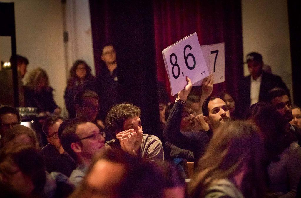 Das Publikum entscheidet: Einige Zuschauer können anhand von Schildern ihre Meinung zum vorgetragenen Text äußern. Foto: Lichtgut/Max Kovalenko