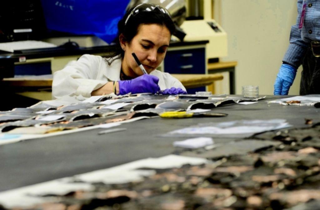 Eine Mitarbeiterin der US-Behörden prüft verbrannte Teile eines Dreamliners. Foto: AFP