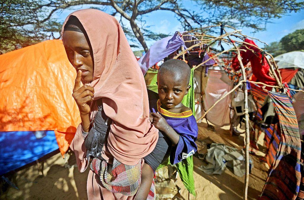 Eine somalische Frau, die in einem Flüchtlingslager untergebracht ist,  trägt ihr kleines Kind auf dem Rücken. Foto: