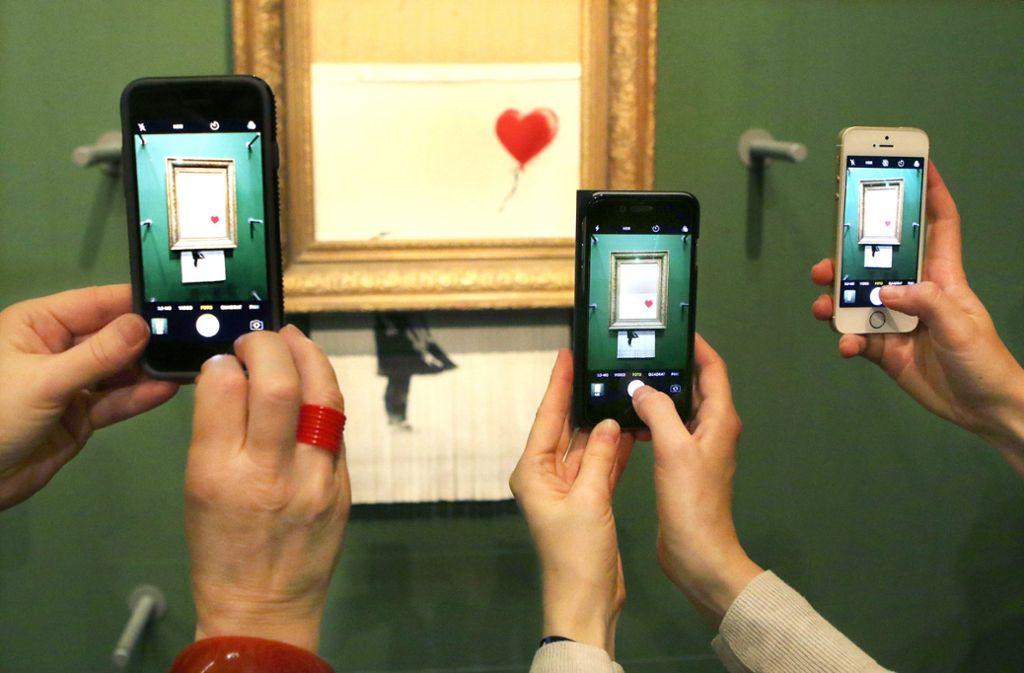 Im Museum wird immer mehr fotografiert – nicht nur vor dem Banksy Schredderbild. Foto: epd