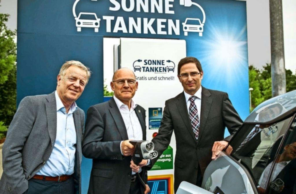 Verkehrsminister Winfried Hermann schließt,   assistiert von Bürgermeister Martin Schairer (links) und Aldi-Manager Karl-Heinz Krehl, das erste E-Auto an. Foto: Lg/Max Kovalenko