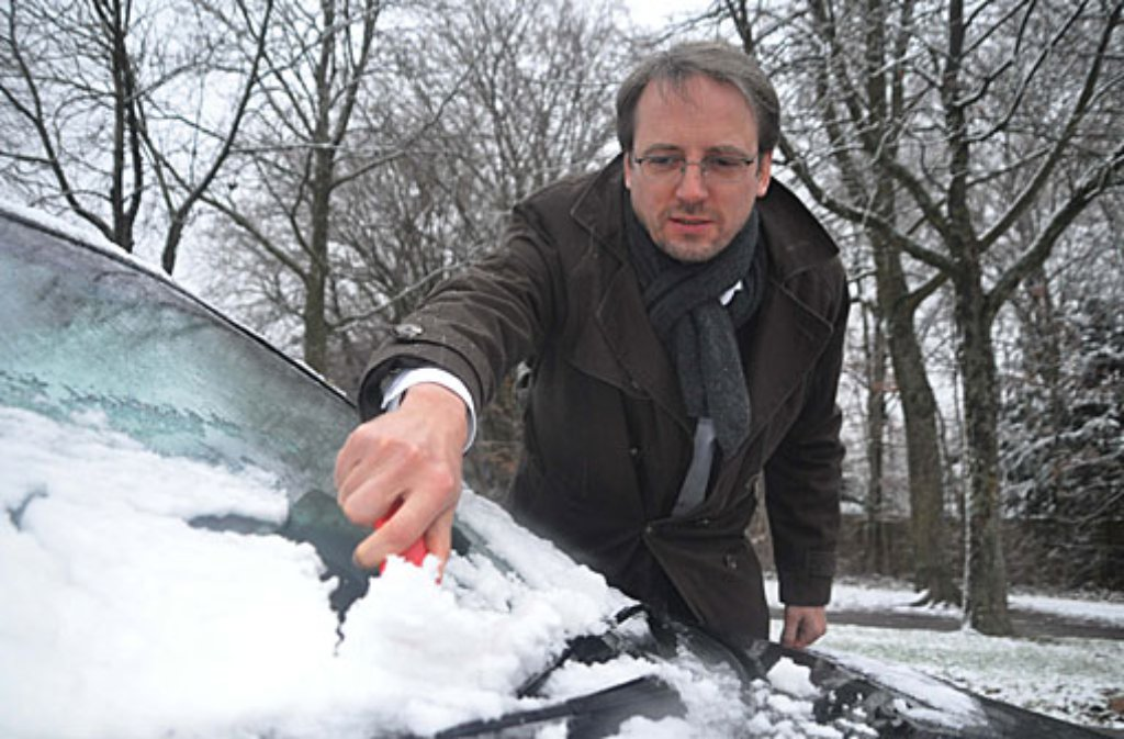 Bernd Milla (43) kehrt den Schnee von seinem Auto. Foto: Fotoagentur Stuttgart