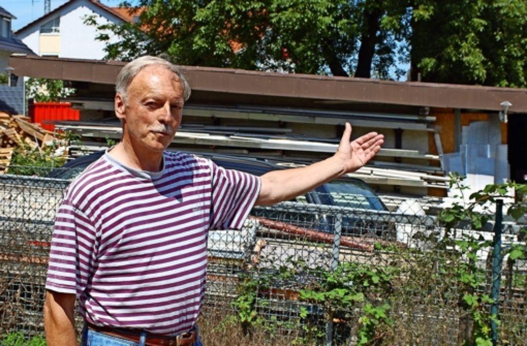 Anwohner Hans Alber zeigt das Materiallager auf dem Nachbargrundstück Foto: Schmierer
