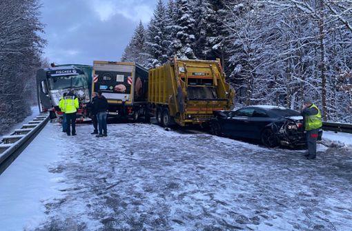 Drei Laster stoßen auf schneebedeckter Straße zusammen