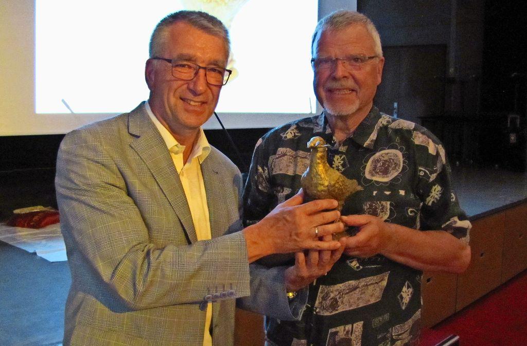 Der Aidlinger Bürgermeister Ekkehard Fauth (links) übergibt die Goldene Friedenstaube an den Vorsitzenden der Waldenbucher EineWelt-Gruppe Burkhard Wolf. Foto: Claudia Barner