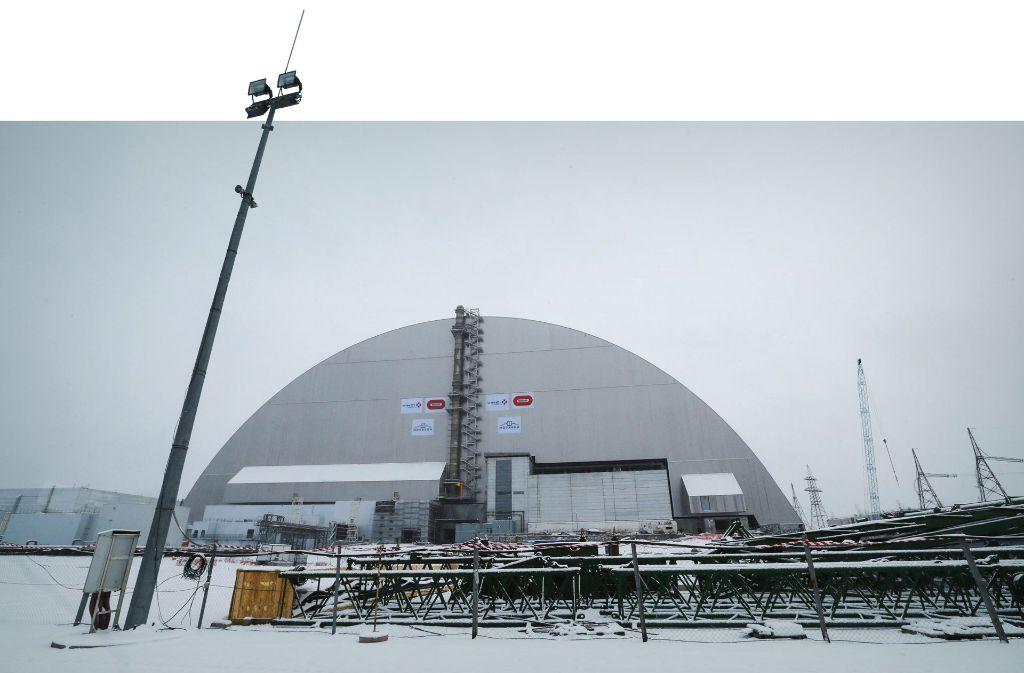 Über den 1986 explodierten Block des Kernkraftwerks von Tschernobyl ist jetzt eine  riesige Schutzhülle in ihre endgültige Position geschoben worden Foto: dpa