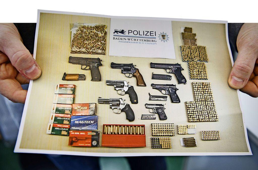 Ein Polizist zeigt, was die Kollegen in Baden-Württemberg an Waffen und Munition beschlagnahmt haben. Foto: dpa