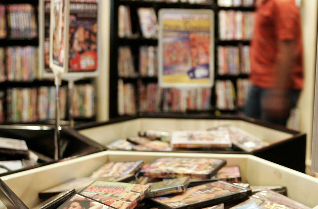 """Ein Kunde schaut sich  in Hamburg in einem """"Beate Uhse"""" Geschäft das angebotene pornografische Filmmaterial an (Archivbild von 2005).) Foto: Kai-Uwe Knoth/AP"""